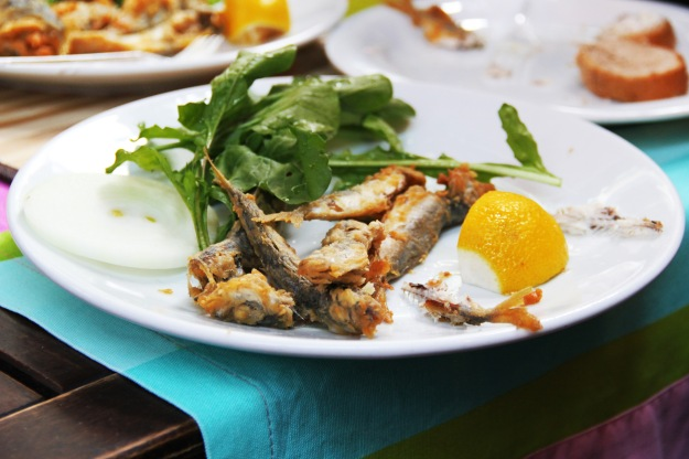 Fried sardines with lemon and arugula